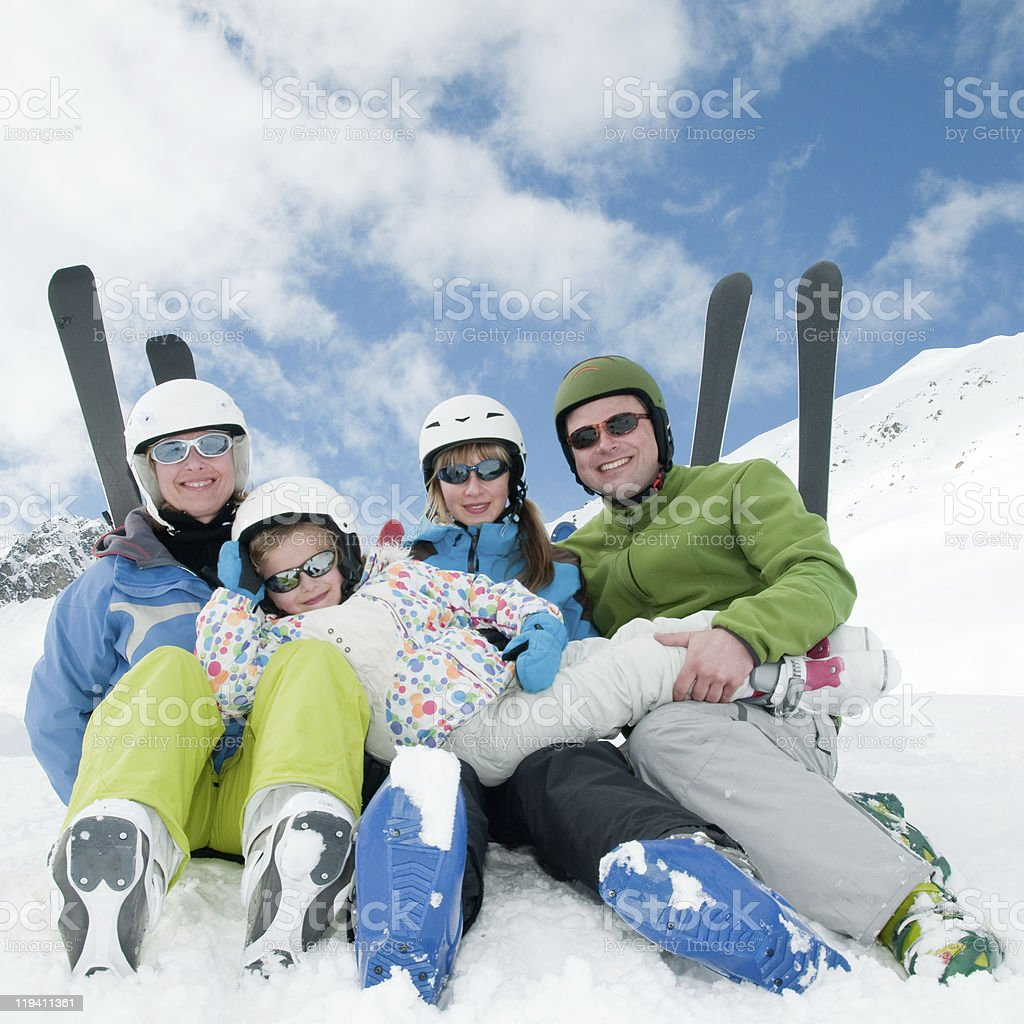 A family sitting in the snow wearing skiing gear stock photo