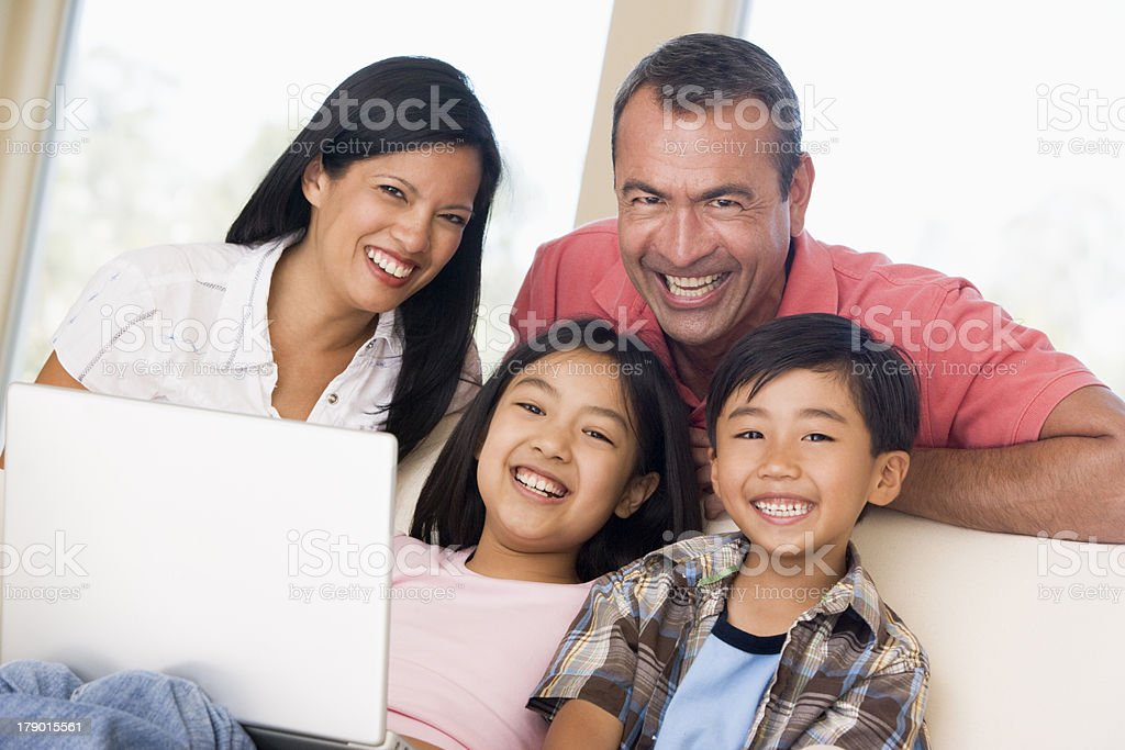 A family sitting on a couch looking at a white laptop royalty-free stock photo