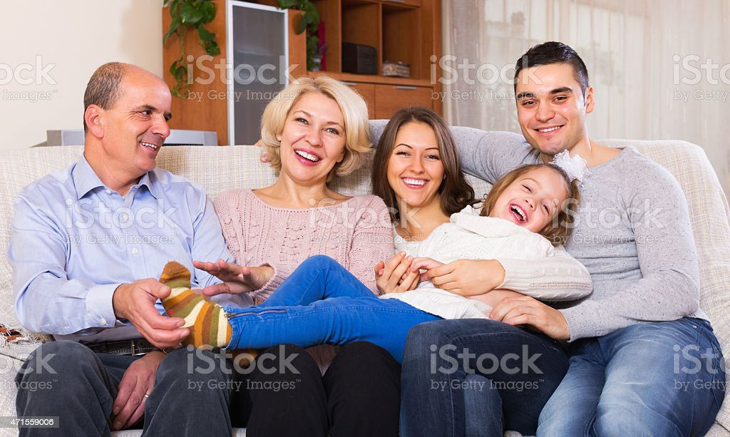 Family sitting on couch in living room stock photo