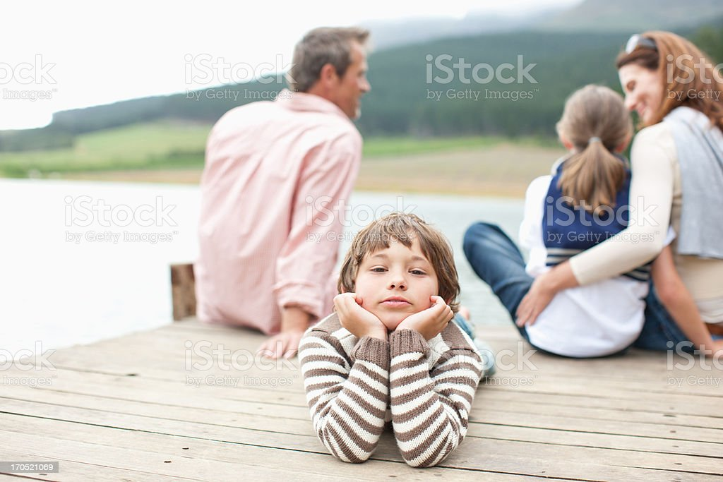 Family sitting on pier by lake royalty-free stock photo