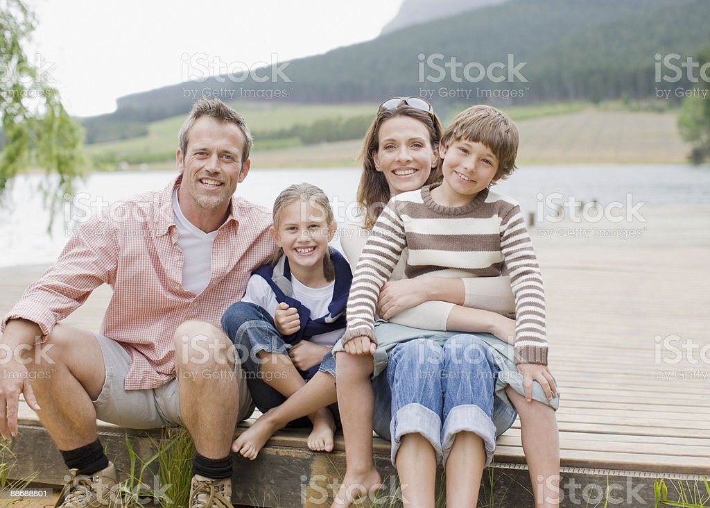 Family sitting on pier by lake stock photo