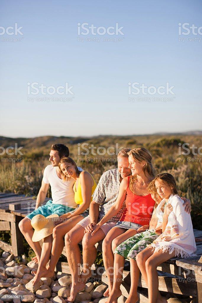 Family sitting on pier near beach royalty-free stock photo