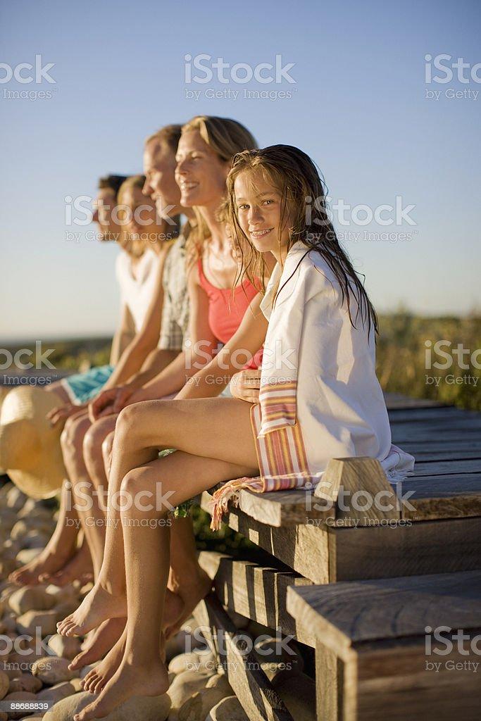 Family sitting on pier near beach stock photo