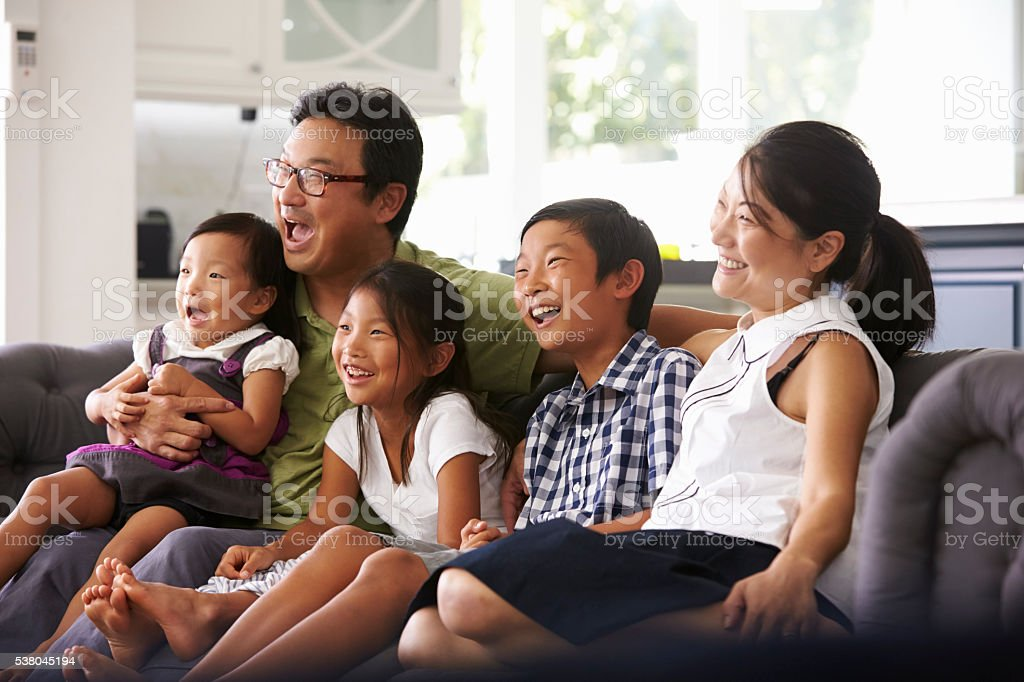 Family Sitting On Sofa At Home Watching TV Together stock photo