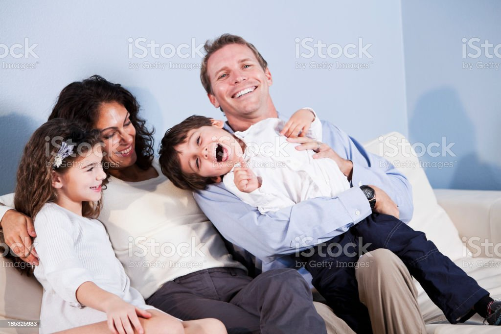 Family sitting on sofa, laughing stock photo