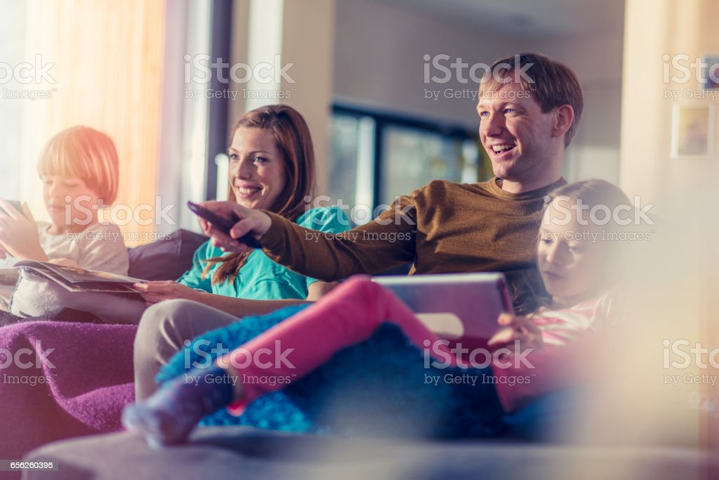 Family sitting on sofa stock photo