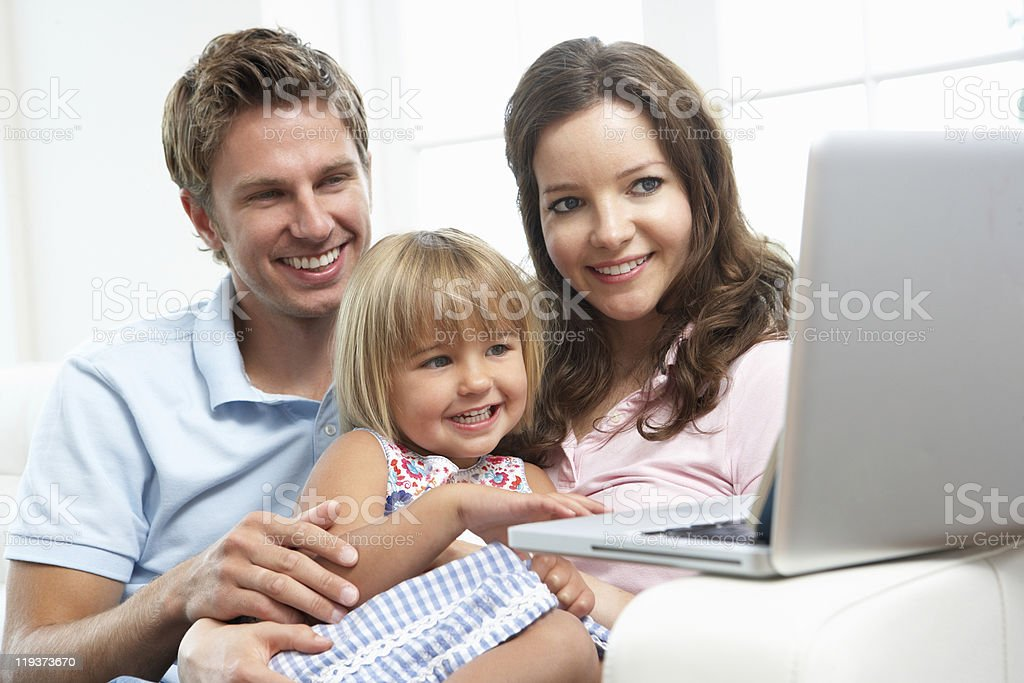 Family Sitting On Sofa Using Laptop At Home royalty-free stock photo