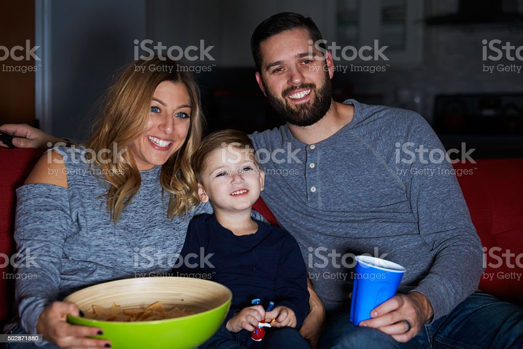 Family Sitting On Sofa Watching Television Together stock photo