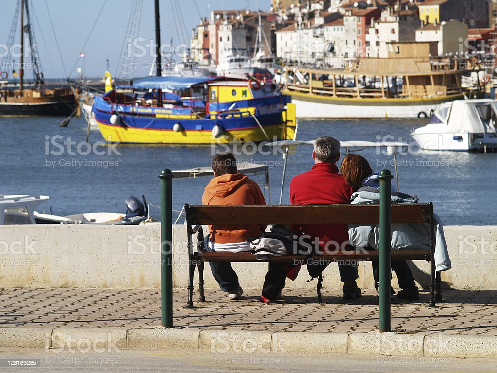 Family sitting on the bench at Rovinj Harbor stock photo