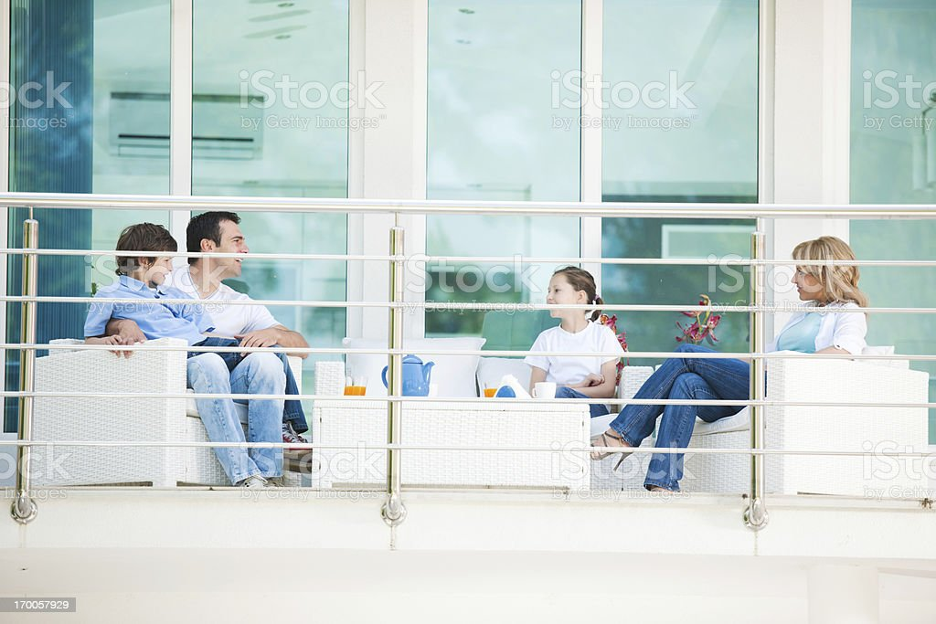 Family sitting on the terrace, to spend time together. royalty-free stock photo