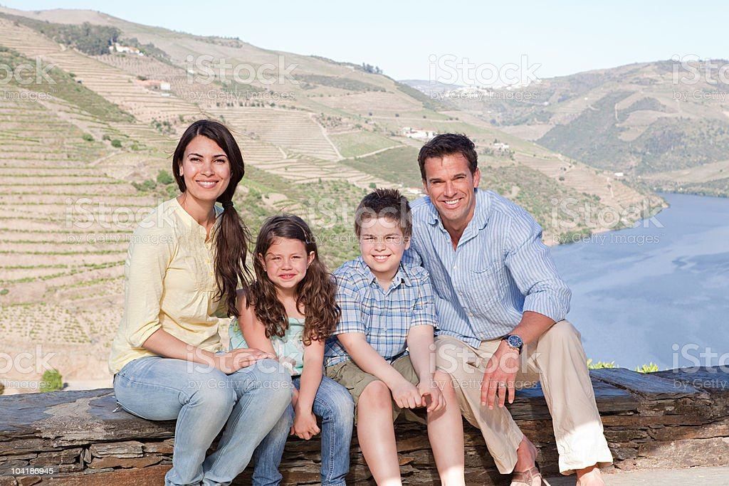Family sitting on wall on holiday royalty-free stock photo