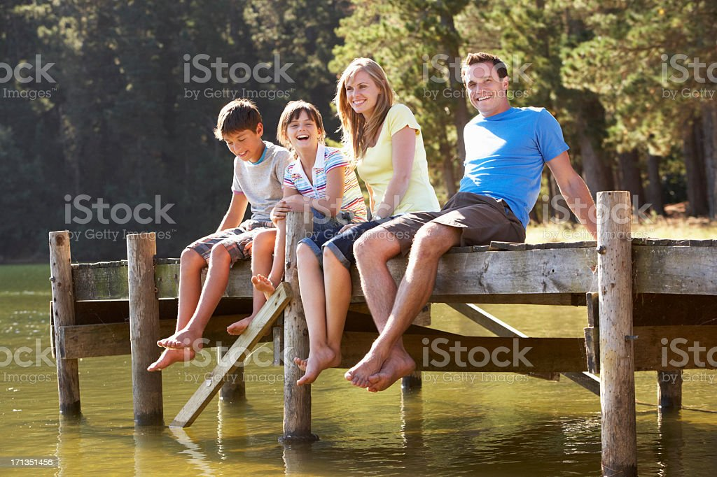 Family Sitting On Wooden Jetty Looking Out Over Lake stock photo