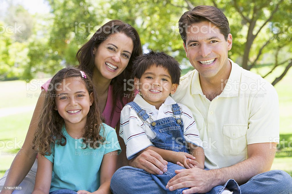 Family sitting outdoors smiling stock photo