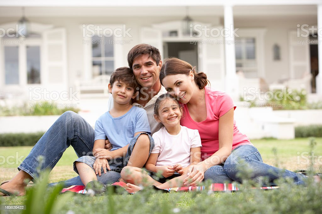 Family Sitting Outside House On Lawn stock photo