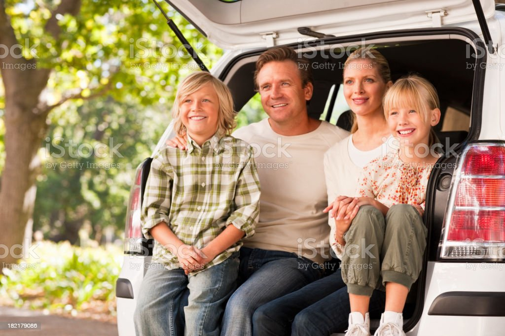 Family sitting together at the hatchback of a van royalty-free stock photo
