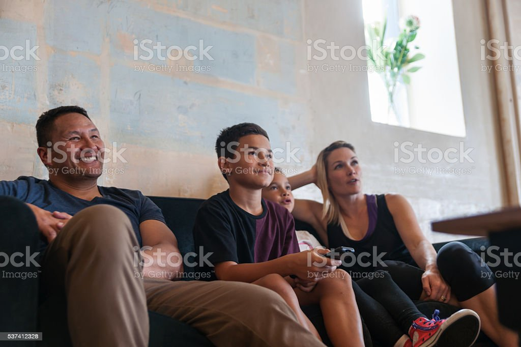 Family sitting together in lounge stock photo