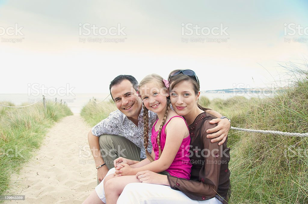 Family sitting together on beach stock photo