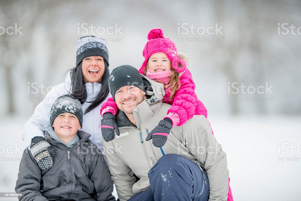Family Sitting Together Out in the Snow stock photo
