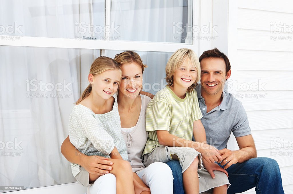 Family sitting together outside house royalty-free stock photo