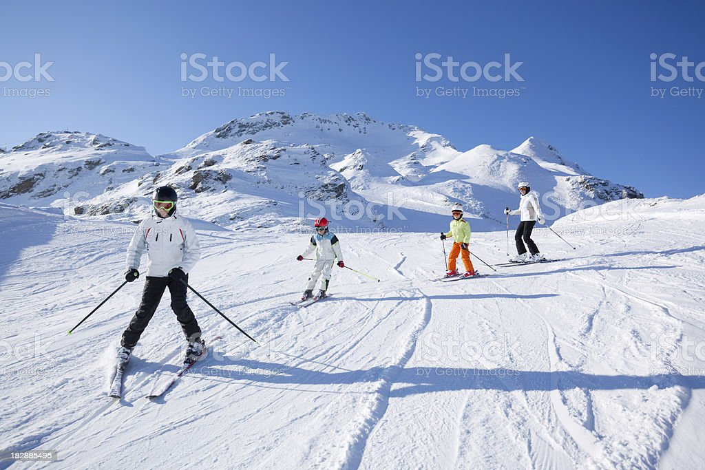 family skiing on sunny day royalty-free stock photo
