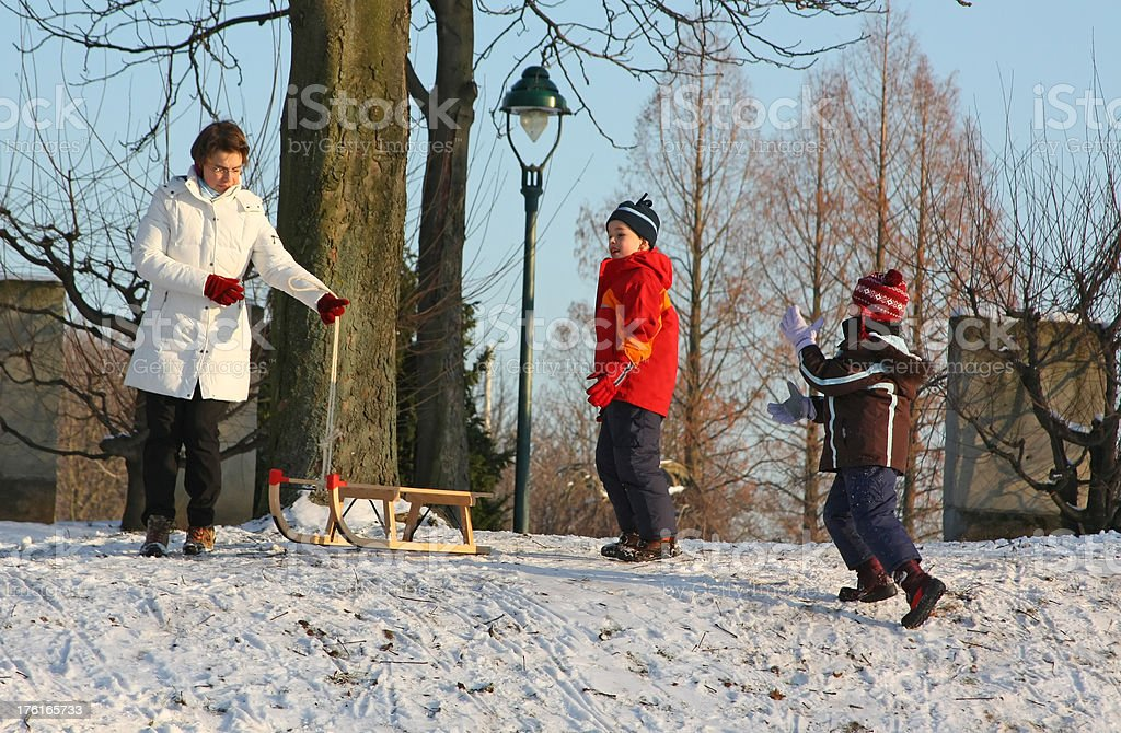 Family sledding fun (adult and two children) royalty-free stock photo