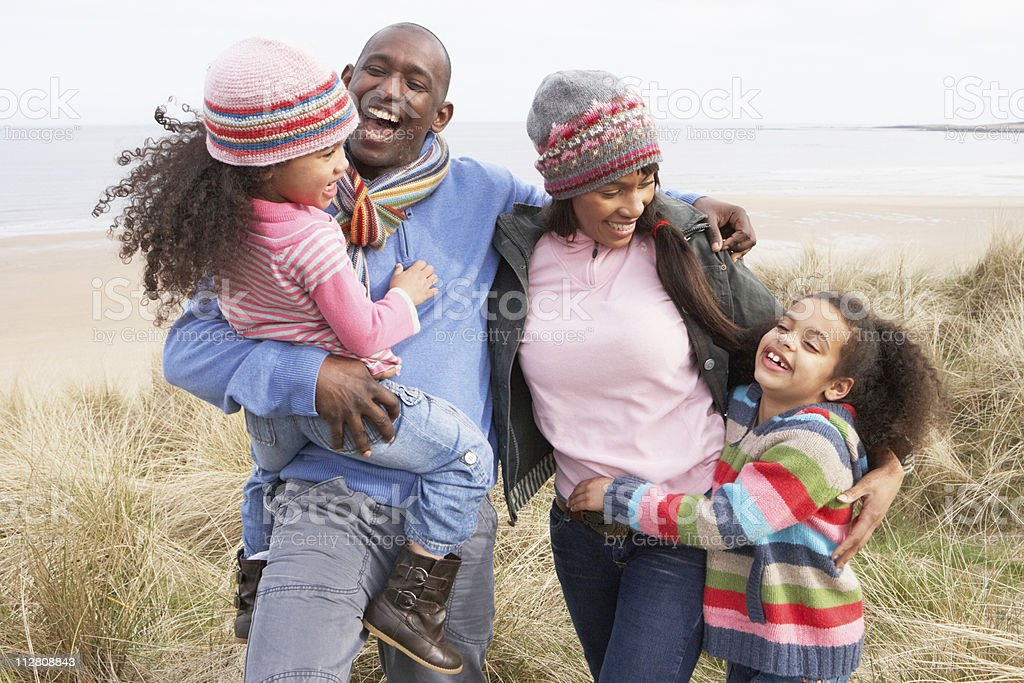 Family smiling and walking along the dunes in autumn stock photo