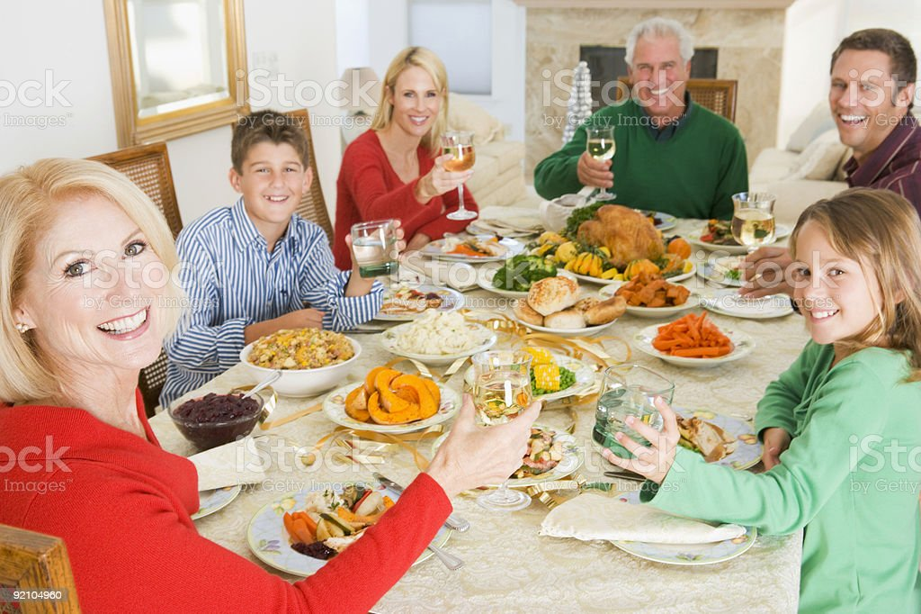 A family smiling at the camera during Christmas dinner royalty-free stock photo