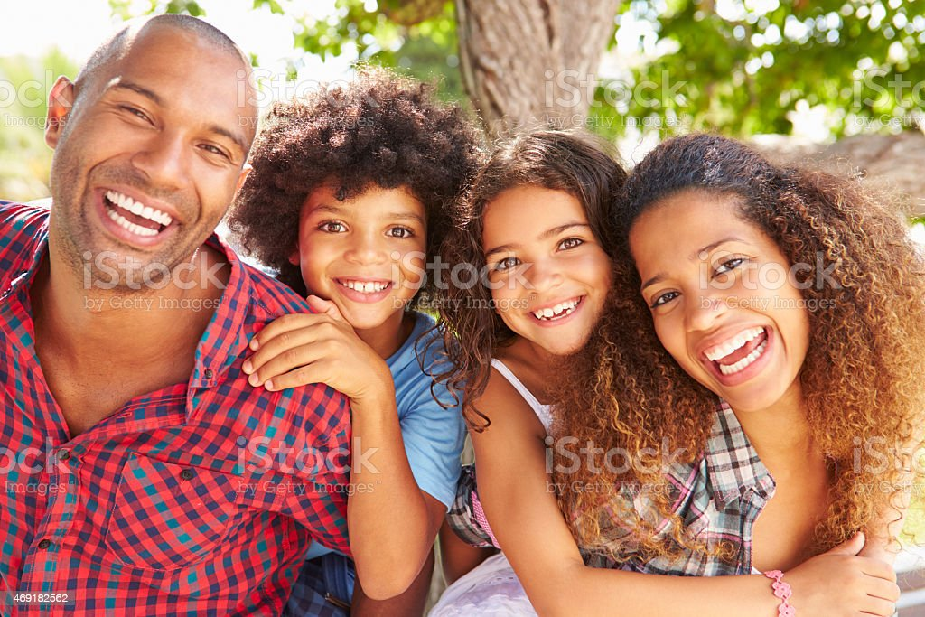 Family smiling outdoors and kids receiving piggyback rides stock photo