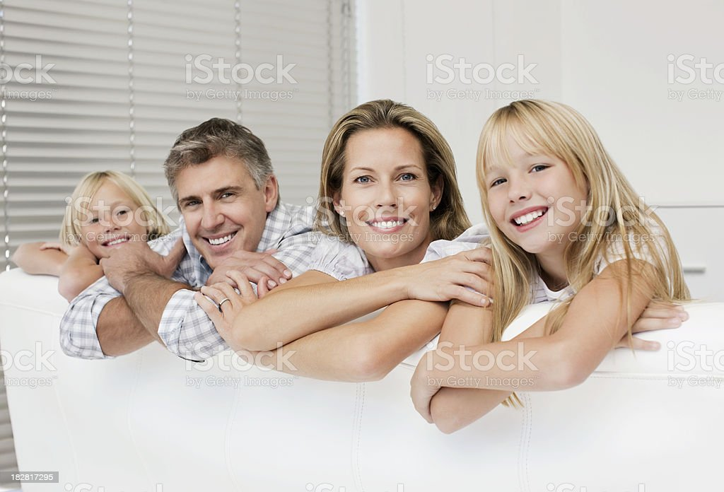 Family Smiling Over the Back of a Couch royalty-free stock photo