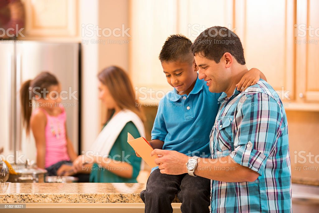 Family. Son shows dad card he made.  Mom, daughter background. stock photo