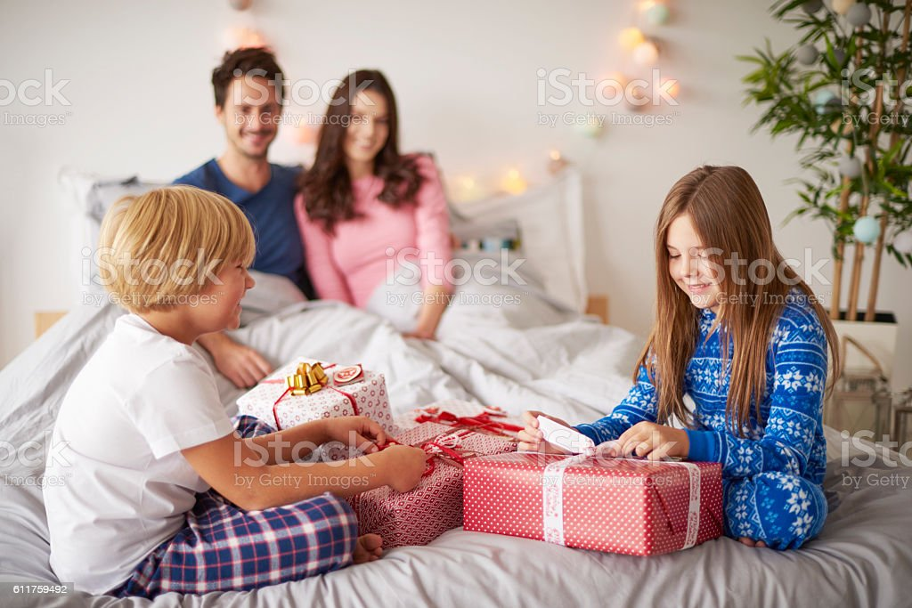 Family spending Christmas morning in the bed stock photo