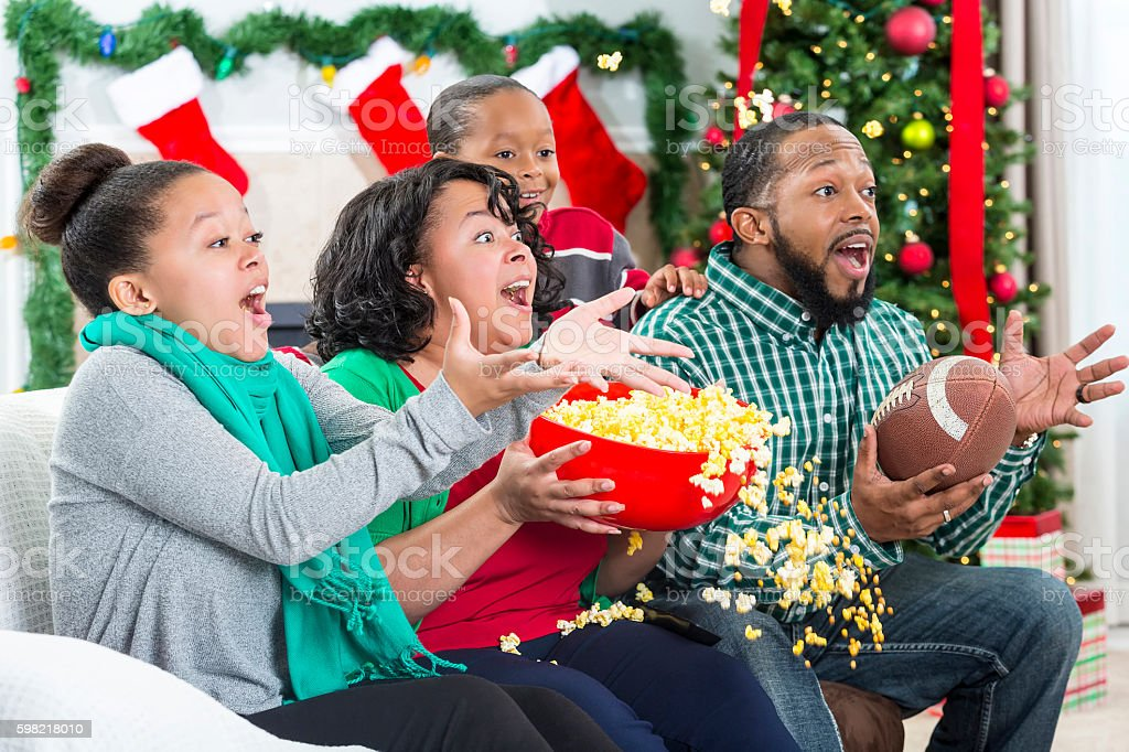 Family spills popcorn while watching excited football game stock photo