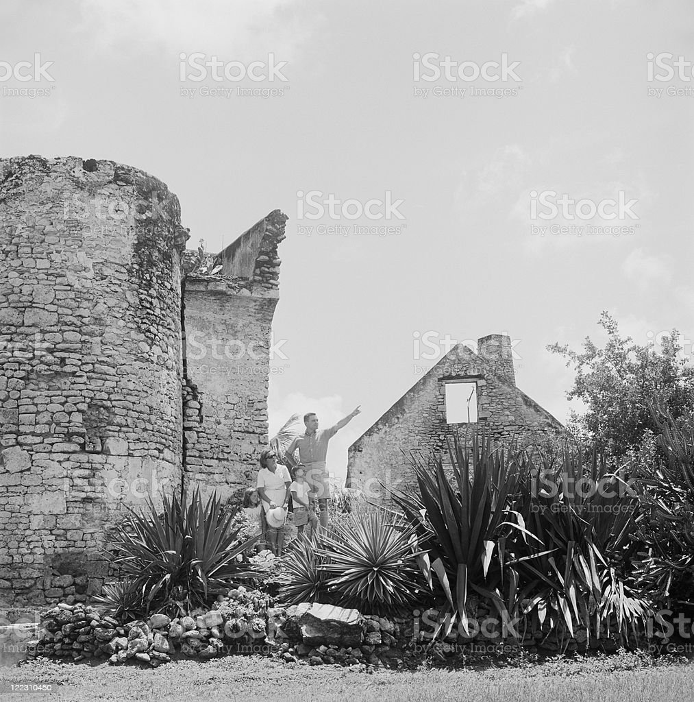 Family standing beside old ruined, father pointing royalty-free stock photo