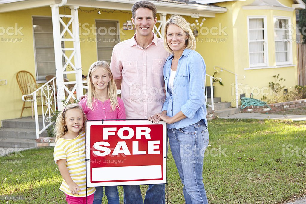 Family Standing By For Sale Sign Outside Home royalty-free stock photo