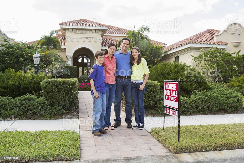 Family Standing By House For Sale Sign royalty-free stock photo