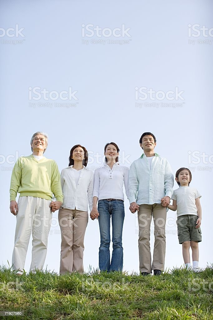 Family standing holding hands royalty-free stock photo