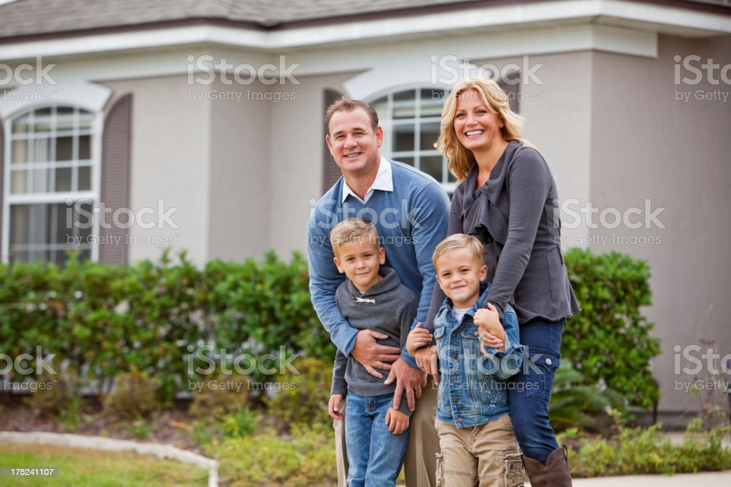 Family standing in front of house royalty-free stock photo