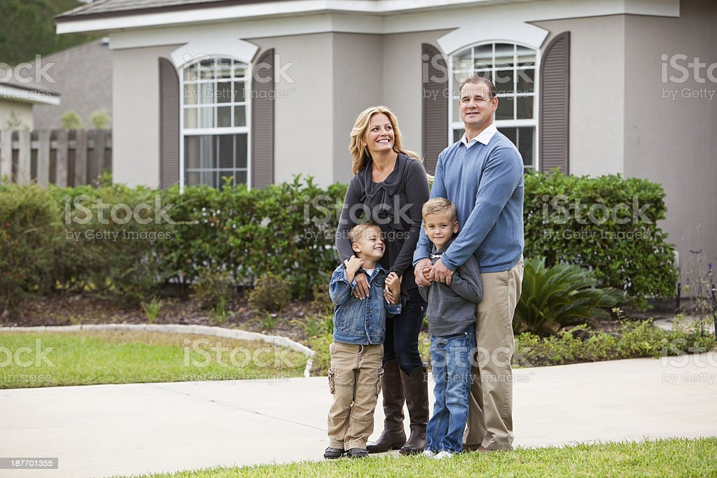 Family standing in front of house stock photo
