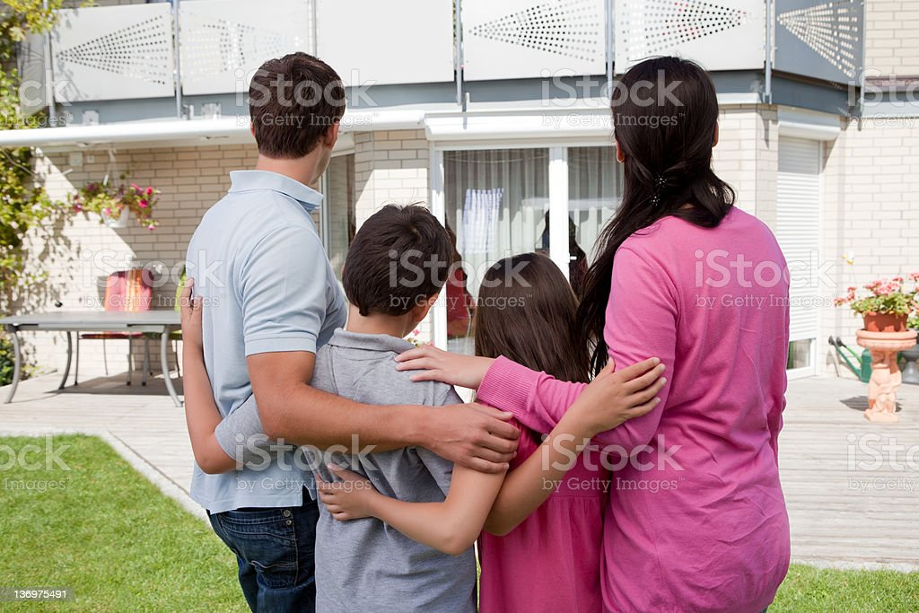 Family standing in front of their house royalty-free stock photo