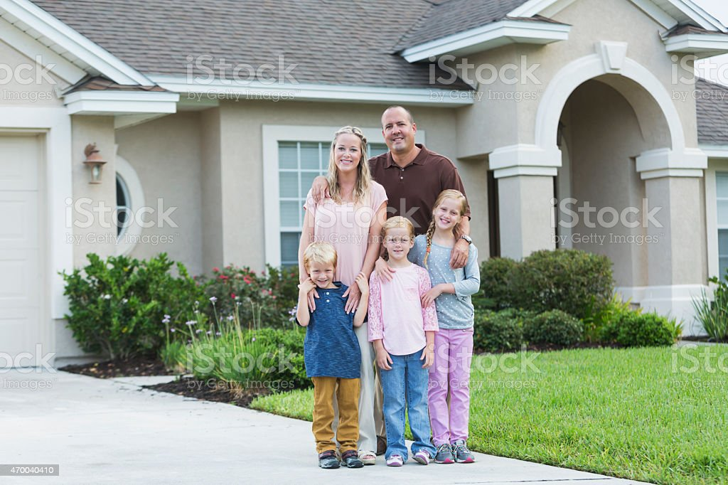 Family standing in front yard of home stock photo