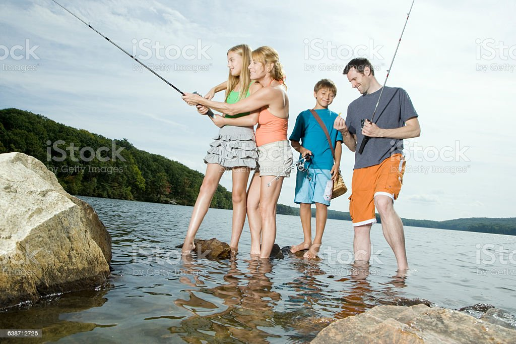 Family standing in lake fishing together stock photo