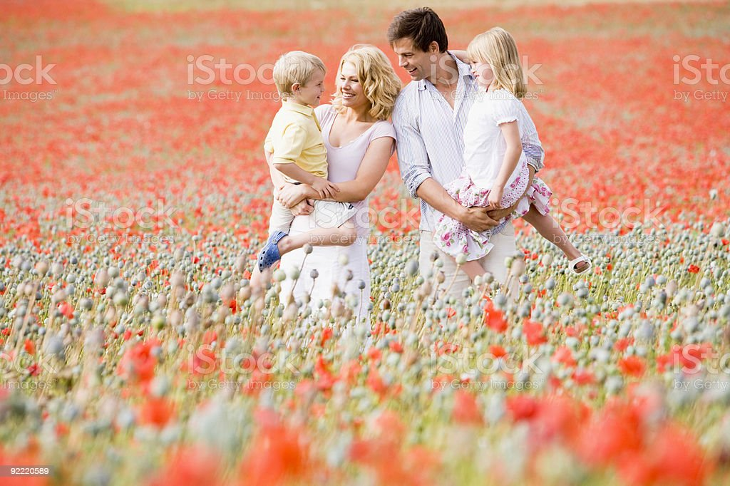 Family standing in poppy field smiling royalty-free stock photo