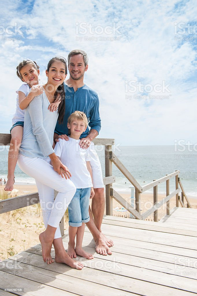 family standing on a wood pontoon deck by the sea stock photo