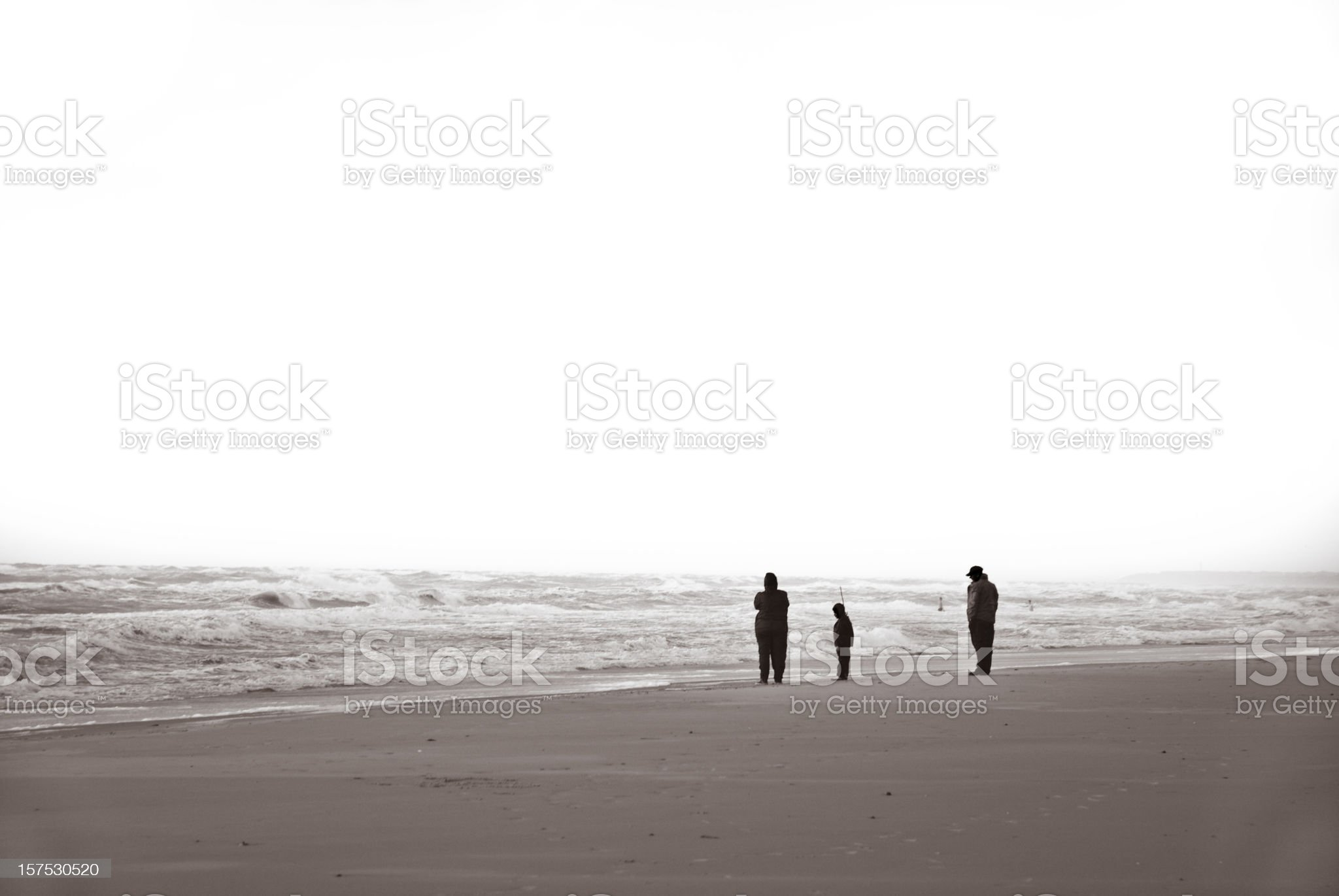 Family standing on beach staring at the sea royalty-free stock photo