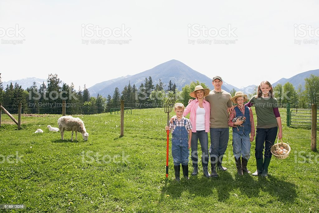 Family standing side by side on farm stock photo