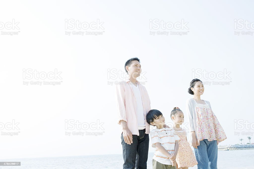 Family standing still at beach stock photo