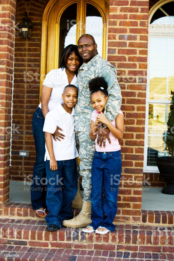 A family standing together on the front steps of their home royalty-free stock photo