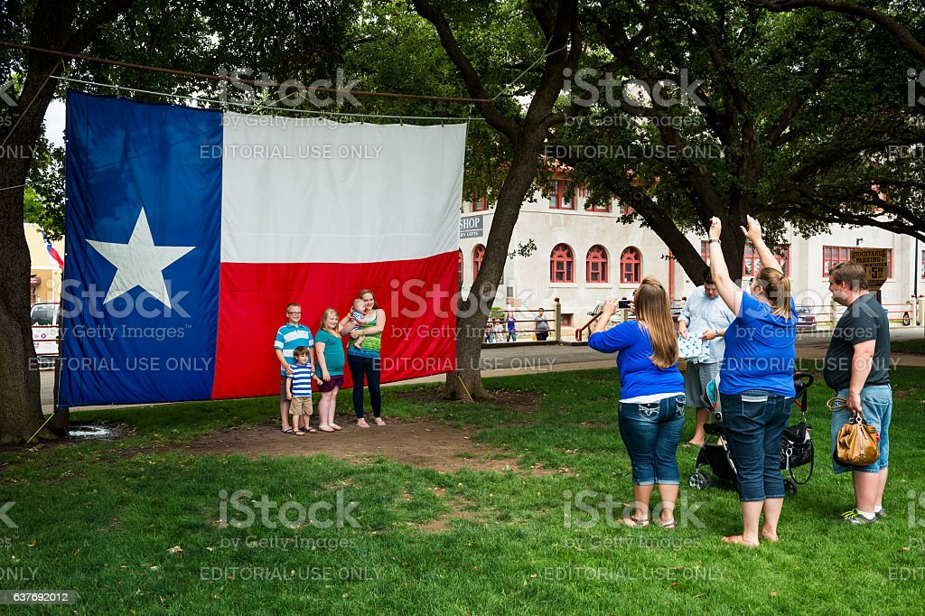 Family taking a photo in front of the Texas Flag stock photo