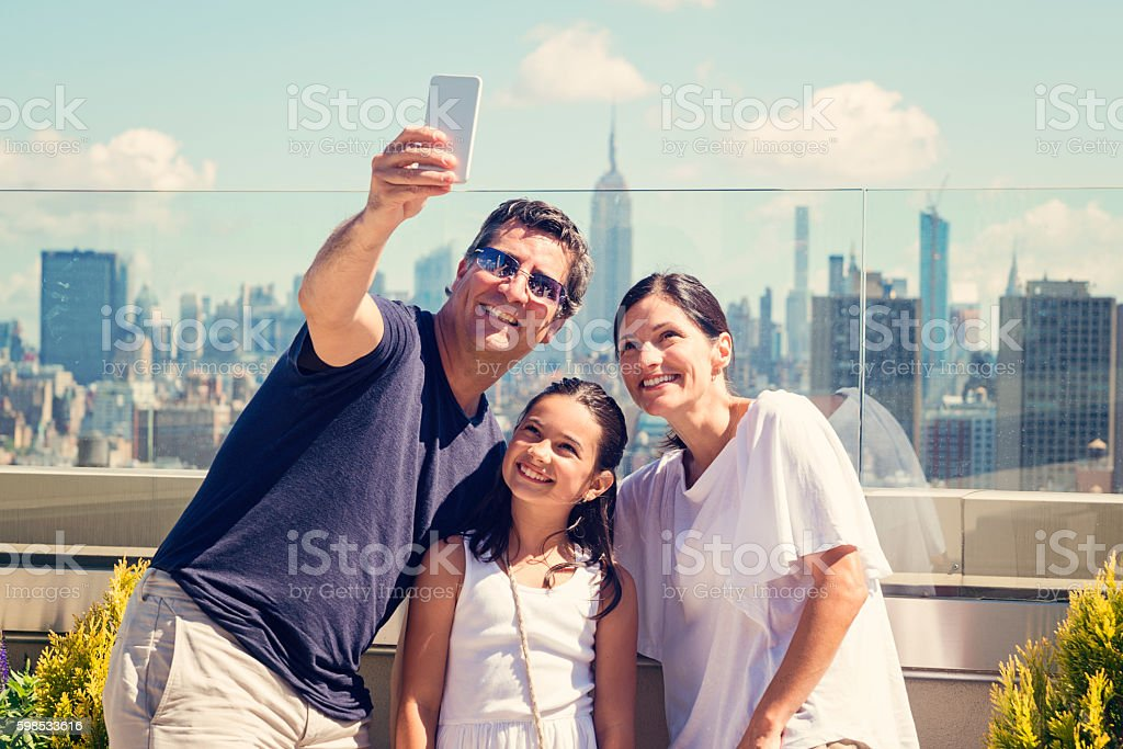 Family taking selfie on a rooftop with New-York skyline. stock photo