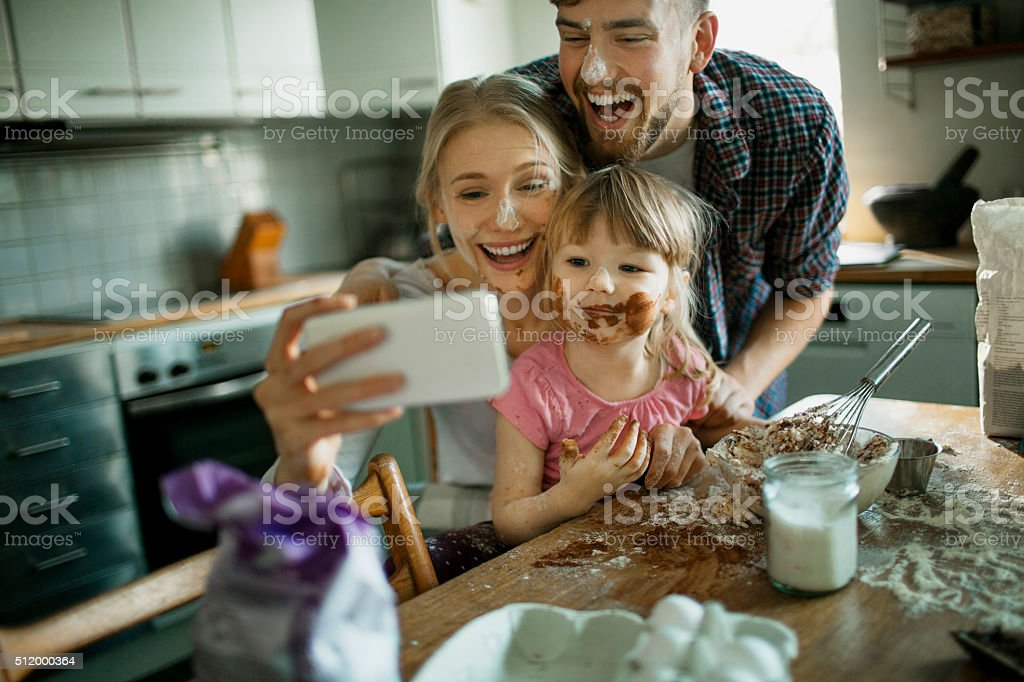 Family taking selfie while baking stock photo